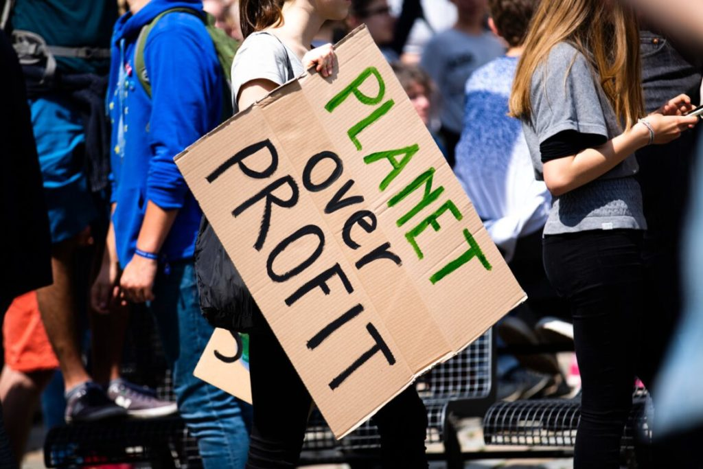 Image of a sign from Berlin protest reading 'Planet Over Profit' taken from climate change and sustainability blog, https://jungle-dancer.com/planet-over-profit-myth-or-fact-can-we-have-both/
